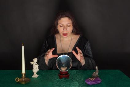 Eine dunkel gekleidete Frau blickt in eine Glaskugel