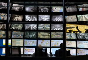 ecurity monitoring control console room with a wall of screens and two workers back silhouettes