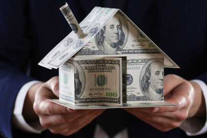 Model of house made of money in male hands on dark background
